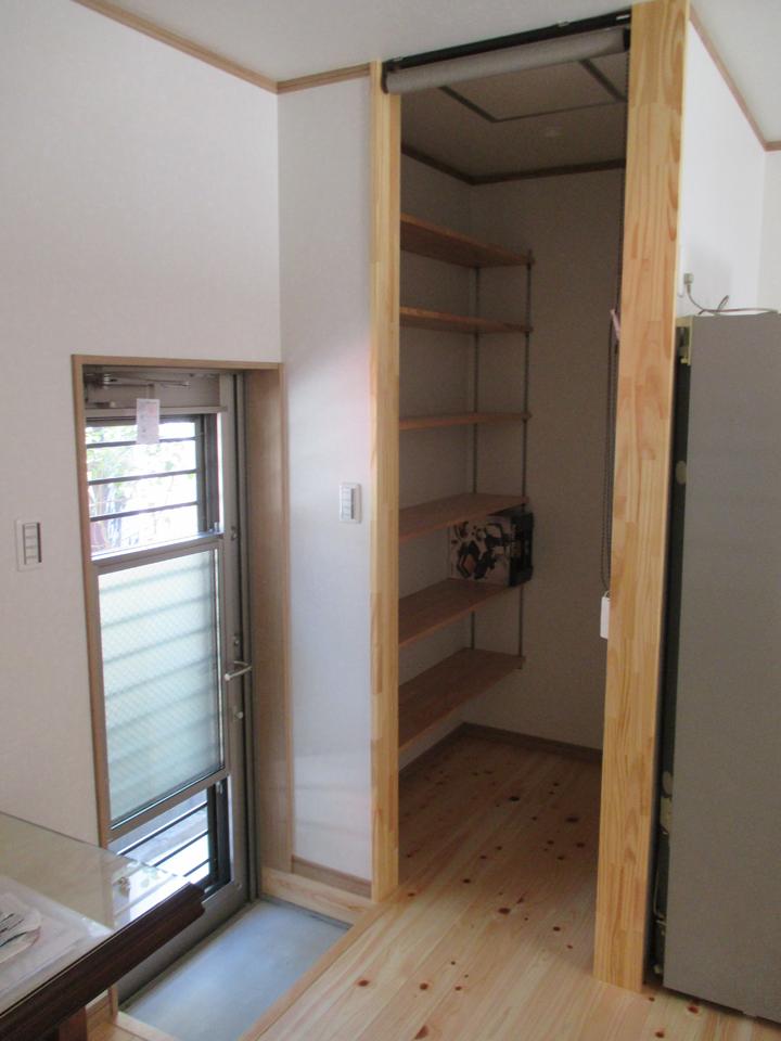 キッチンの裏側の小部屋にも棚を作りました。長い扉は裏側の出入り口です。